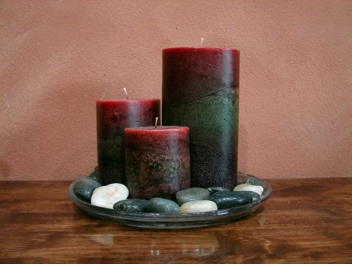 tres velas en un plato con piedras